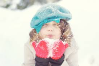 Young girl blowing snow at the camera.