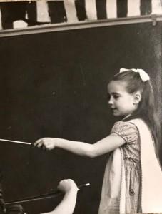 Young girl conducting music class