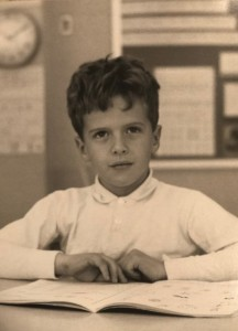 Young boy reading a book in class